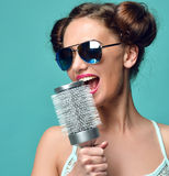 Happy fashion brunette woman singing with big hair brush in mode Royalty Free Stock Photo