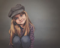 Happy Fashion Child with Copyspace. A little fashion girl with long hair and blue eyes wearing a hat is smiling with copyspace on a gray background for a royalty free stock images