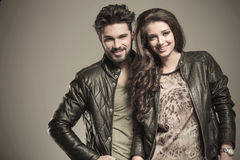 Happy fashion couple in leather jackets smiling. To the camera in studio Stock Photos
