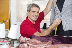 Happy Fashion Designer Measuring Suit On Mannequin. Portrait of happy male fashion designer measuring suit on mannequin at sewing factory Royalty Free Stock Photography