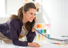 Happy fashion designer in office talking phone. Happy fashion designer in modern office talking phone royalty free stock photography
