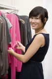 Happy fashion designer standing by clothing rack at store Royalty Free Stock Photos