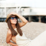 Happy fashion dressed woman in hat rest sitting on a beach. Stock Photos