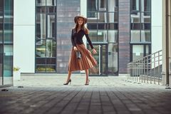 Happy fashion elegant woman wearing a black jacket, brown hat and skirt with a handbag clutch walking on the European royalty free stock photo