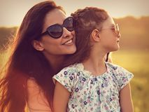 Happy fashion kid girl embracing her mother in trendy sunglasses Stock Photos
