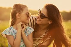 Happy fashion kid girl embracing her mother in trendy sunglasses and looking each other with love on nature background. Closeup royalty free stock photo