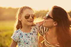 Happy fashion kid girl embracing her mother in trendy sunglasses and looking each other with love on nature background. Closeup royalty free stock photography