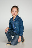 Happy fashion little girl sits Royalty Free Stock Photography