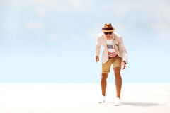 Happy fashion man walking around beach. blue sky background. Cool fashion man in hat and glasses at beach modeling and posing Royalty Free Stock Photos