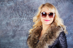 Happy fashion model posing in coat and sunglasses. Portrait of happy young fashion model posing in coat with fur collar and sunglasses, looking at camera and Stock Image