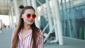 Happy fashion model in red sunglasses walks confident along the street near shopping centre. Summer time.  stock footage