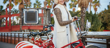 Happy fashion-monger in Barcelona, Spain standing near bicycle Royalty Free Stock Image