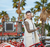 Happy fashion-monger in Barcelona, Spain standing near bicycle Royalty Free Stock Photo