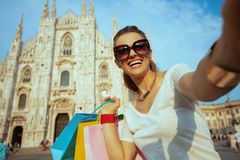 Happy fashion-monger with colorful shopping bags taking selfie. Happy modern fashion-monger in white t-shirt and sunglasses with colorful shopping bags taking stock images