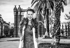 Happy fashion-monger near Arc de Triomf in Barcelona, Spain. In Barcelona for a perfect winter. Portrait of happy elegant fashion-monger in earmuffs near Arc de Royalty Free Stock Photos