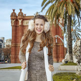 Happy fashion-monger near Arc de Triomf in Barcelona, Spain. In Barcelona for a perfect winter. Portrait of happy elegant fashion-monger in earmuffs near Arc de Royalty Free Stock Images