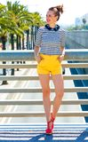Happy fashion-monger outdoors in city looking into distance. Nosing around, having fun. Full length portrait of happy elegant fashion-monger in yellow shorts and Royalty Free Stock Photo
