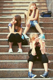 Happy fashion teen girls sitting on steps Royalty Free Stock Photos