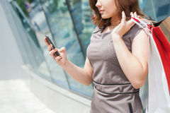 Happy fashion woman with bag using mobile phone, shopping center Stock Photos