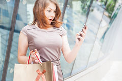 Happy fashion woman with bag using mobile phone, shopping center Royalty Free Stock Photo