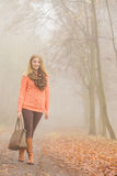 Happy fashion woman with handbag in autumn park Stock Image