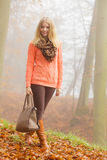 Happy fashion woman with handbag in autumn park Stock Photos