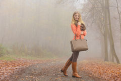 Happy fashion woman with handbag in autumn park Royalty Free Stock Image
