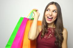 Happy fashion woman lift her shopper bags full of new clothes on white background.  royalty free stock photo