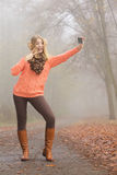 Happy fashion woman in park taking selfie photo. Stock Image