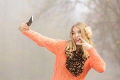 Happy fashion woman in park taking selfie photo. Stock Photo
