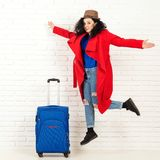 Happy fashion woman ready for travel. Woman jumping against brick wall. Travel and lifestyle concept. Stylish girl in red coat royalty free stock image