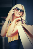 Happy fashion woman with shopping bags calling on mobile phone Royalty Free Stock Photography