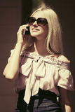 Happy fashion woman in sunglasses calling on mobile phone Royalty Free Stock Images