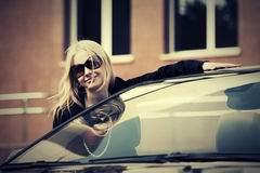 Happy fashion woman in sunglasses next to her car. Happy young fashion woman in sunglasses next to her car Stock Photo
