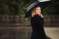 Happy fashion woman with umbrella in the rain Stock Image
