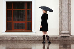 Happy fashion woman with umbrella in a rain Stock Images