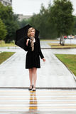 Happy fashion woman with umbrella walking on a city street Stock Images
