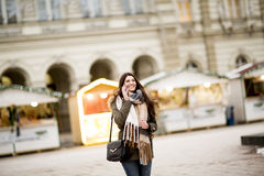 Happy fashion woman using a smart phone on street in winter Stock Image