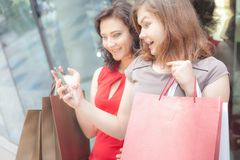 Happy fashion women with bags using mobile phone, shopping center Royalty Free Stock Images