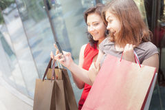 Happy fashion women with bags using mobile phone, shopping center Stock Images