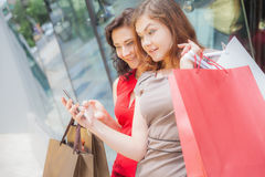 Happy fashion women with bags using mobile phone, shopping center Royalty Free Stock Photography