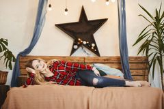 Happy and fashionable blonde model girl with a charming smile in the red plaid shirt and in jeans rests on the wooden stock photo