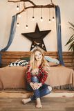 Happy and fashionable blonde model girl with a charming smile in the red plaid shirt and in jeans sits near the wooden royalty free stock images