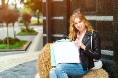 Happy fashionable woman with shopping bags outdoors. People, fashion, lifestyle concept. Positive emotions. Girl enjoying. Purchases. Seasonal sales concept royalty free stock image