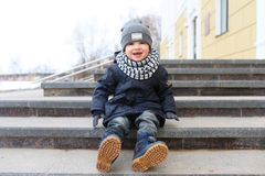 Happy fashionably dressed little boy sitting on stairs outdoors Royalty Free Stock Photos