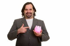 Happy fat Caucasian businessman smiling and holding piggy bank w stock images