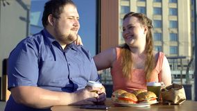 Happy fat couple dating in fast food cafe, unhealthy food, body positive. Stock photo stock image