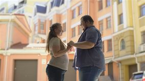 Happy fat couple in love holding hands at urban date, tender relationship