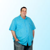 Happy fat man. With blue shirt isolated on blue background stock images
