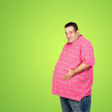 Happy fat man with blue shirt. And a green background Royalty Free Stock Image